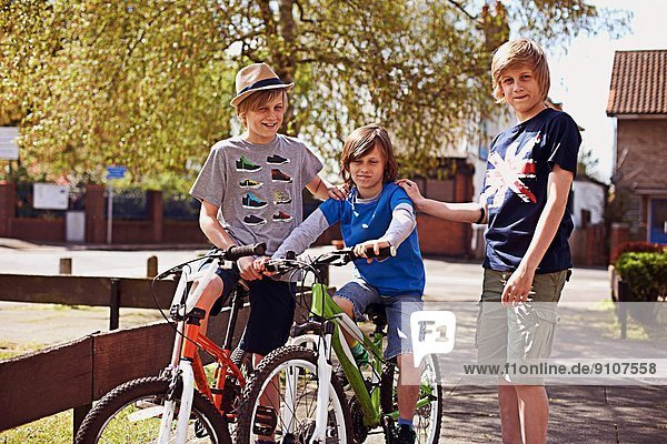 Portrait of boys on pavement with bikes