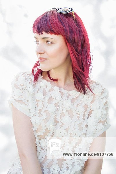 Porträt einer weiblichen jungen Frau mit rosa Haaren