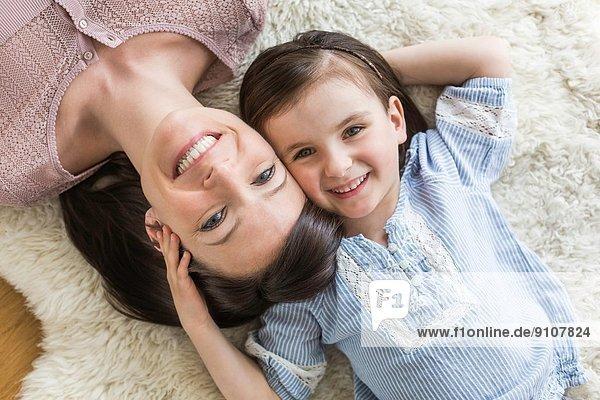 Mutter und Tochter auf Fellteppich liegend  Draufsicht