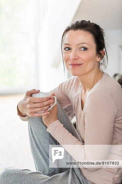 Mittlere erwachsene Frau mit Kaffee