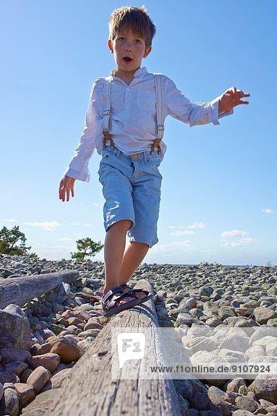 Junge beim Balancieren am Strand