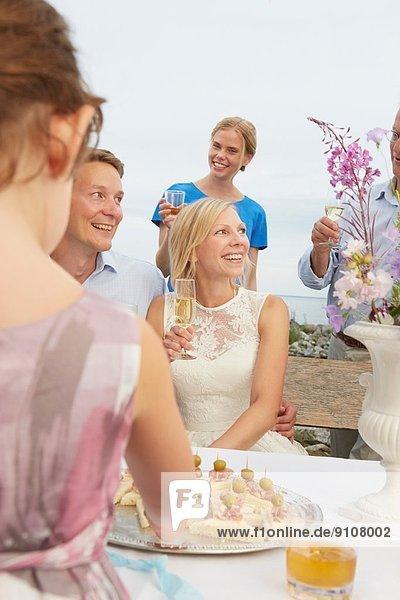 Mittleres erwachsenes Paar  das einen Toast mit einer Gruppe von Freunden bei der Hochzeitsfeier ausspricht.