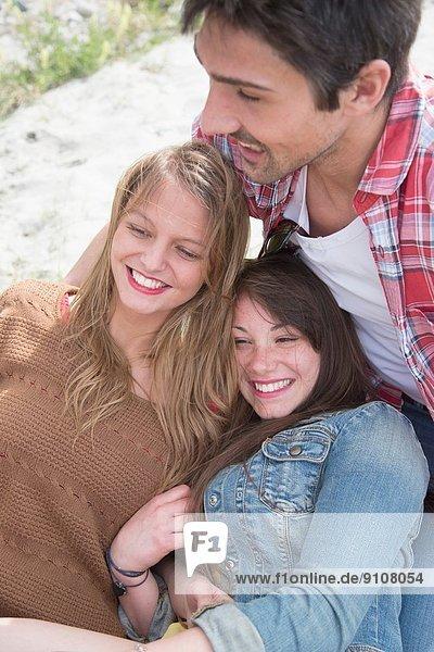 Gruppe von drei jungen erwachsenen Freunden beim Lachen
