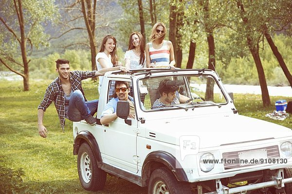 Freunde sitzen auf dem Rücksitz eines Geländewagens.