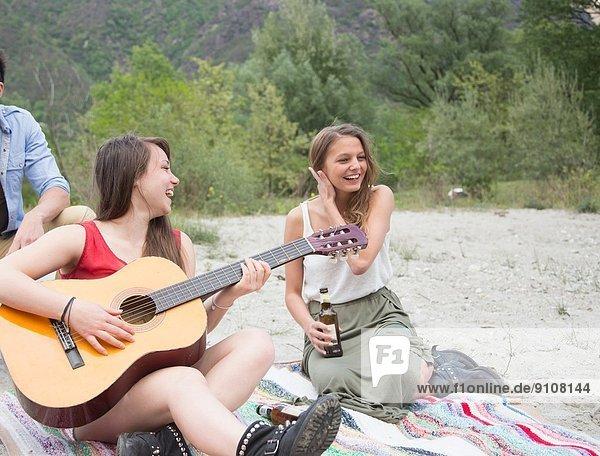 Freunde sitzen auf dem Feld  spielen Gitarre
