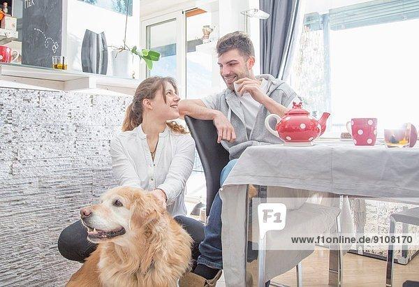 Junges Paar beim Frühstück  mit Hund Junges Paar beim Frühstück, mit Hund