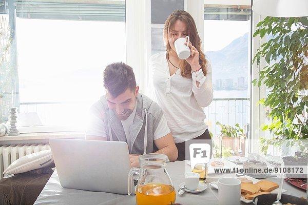 Junger Mann beim Frühstück und mit Laptop