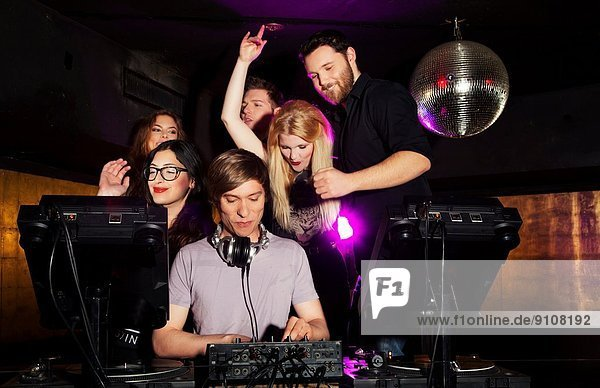 Group of friends watching DJ in nightclub