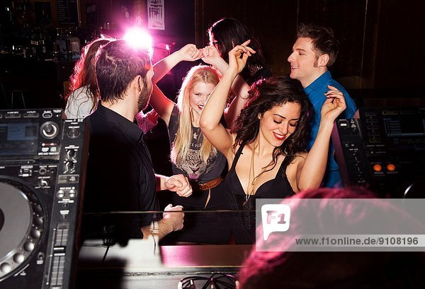 Group of friends dancing in front of DJ in nightclub