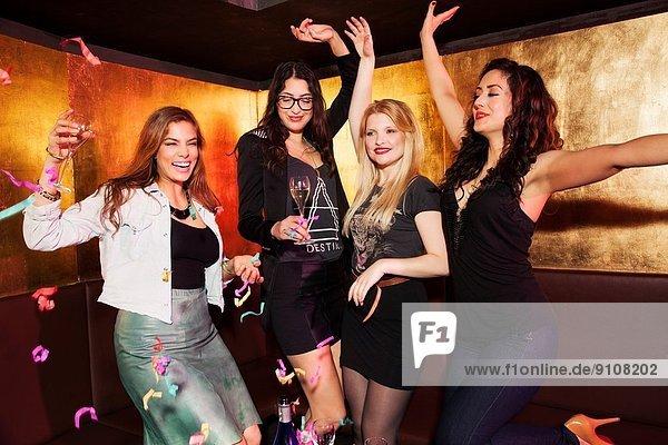 Four female friends celebrating in nightclub