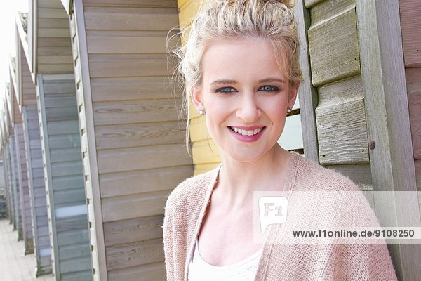 Portrait of young woman leaning against beach hut