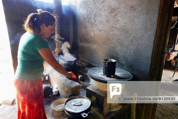 El Salvador. Projects of JDS in Jujutla  community of Oja de Sal. The family of Jose Saul Sanchez (41)  his wife Felipa Flores Tovar (39) and six children  Hazzid (5)  Krissia (6)  Danilo (12)  Ericka (13)  Erick (15) and Silvia 17. Silvia cooking on eco stove.