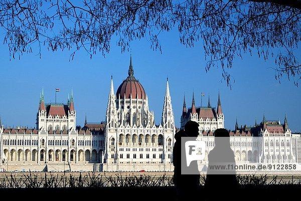 Budapest  Hauptstadt  Mensch  Sitzmöbel  Menschen  Baum  Silhouette  Gebäude  Monument  frontal  Parlamentsgebäude  früh  groß  großes  großer  große  großen  bauen  Ungarn  Gotik  zusammenbauen  Jahrhundert  Sitzplatz