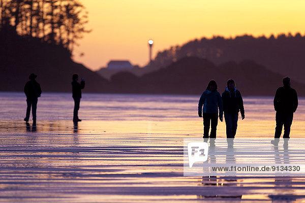 Evening strollers make their way along Chesterman beach. Long Beach  Tofino  Vancouver Island  British Columbia  Canada