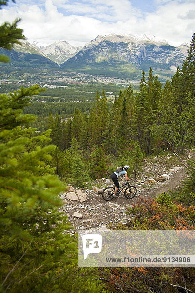 A female mountain biker riding the Highline trail in Canmore  AB