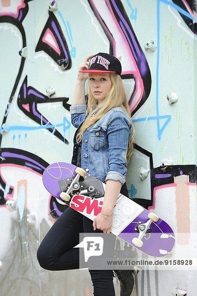 Junge Frau an einer Graffitiwand  Nürnberg  Bayern  Deutschland  Europa