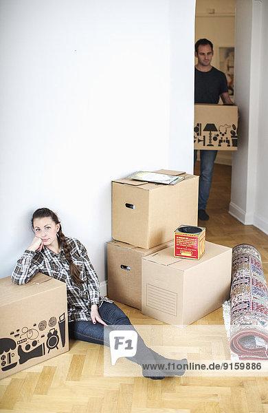 Volle Länge der Frau  die auf dem Boden sitzt  während der Mann einen Karton im neuen Haus trägt.
