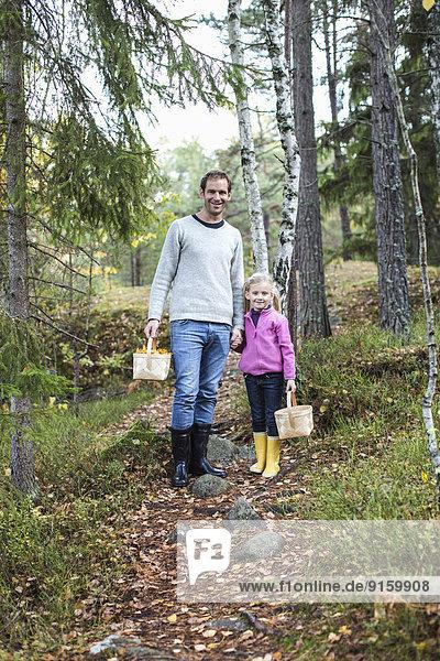 Ganzaufnahme von Vater und Tochter mit Körben im Wald