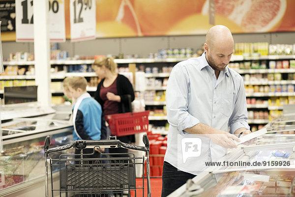 Mittlerer Erwachsener Mann untersucht Produkt mit Familie im Hintergrund im Lebensmittelgeschäft