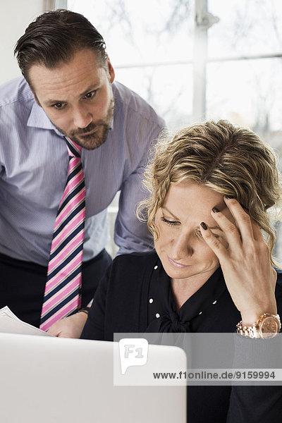 Senior Geschäftsleute suchen Laptop im Büro