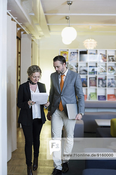 Mature businesswoman and businessman with paperwork in creative office