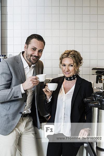 Porträt von lächelnden Geschäftsleuten beim Kaffee in der Küche