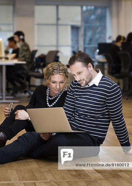 Intelligent gekleidete Geschäftsleute  die den Laptop benutzen  während sie im Büro auf dem Boden sitzen.
