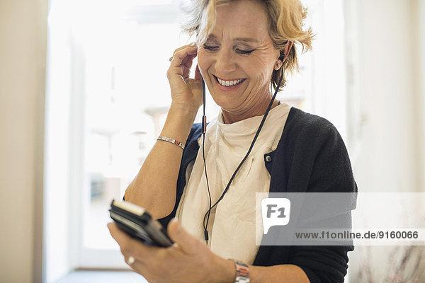 Lächelnde Geschäftsfrau beim Musikhören über das Handy im Büro