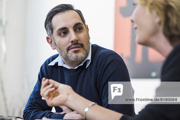 Geschäftsmann hört der Kollegin bei einem Treffen im Büro zu
