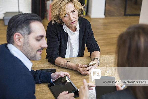 Geschäftsleute mit digitalen Tabletts diskutieren am Schreibtisch im Büro