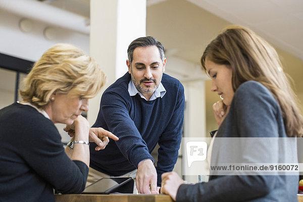 Geschäftsmann Planungsstrategie mit Kolleginnen am Schreibtisch in der Bürobesprechung