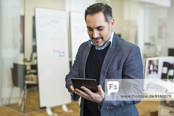 Mittlerer Erwachsener Geschäftsmann mit digitalem Tablett im Büro