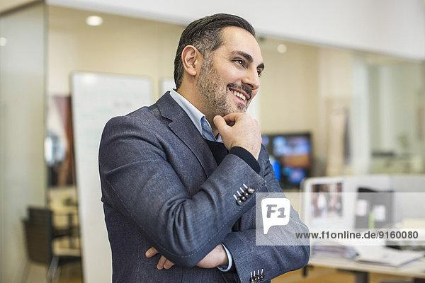 Lächelnder mittelständischer Geschäftsmann mit Hand am Kinn  der im Büro wegschaut.