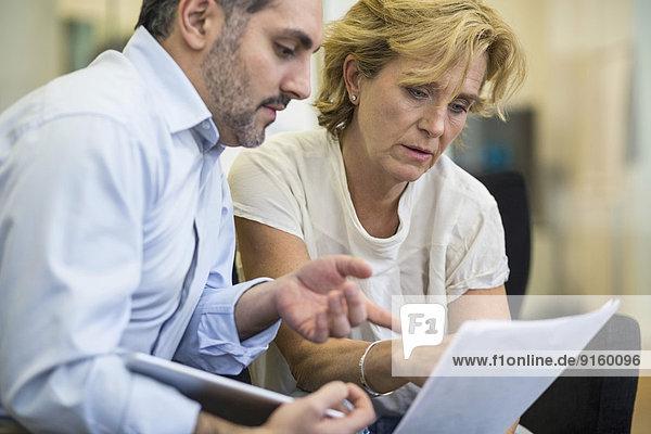 Geschäftsleute  die über das Dokument im Büro diskutieren