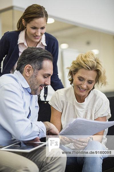 Lächelnde Geschäftsleute planen Strategie im Büromeeting
