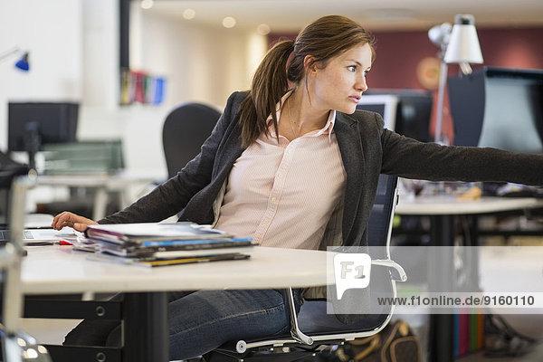 Geschäftsfrau schaut weg  während sie im Büro am Schreibtisch sitzt.
