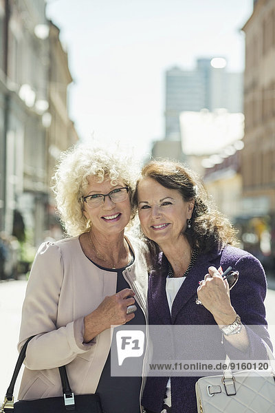 Portrait of happy senior women standing on street