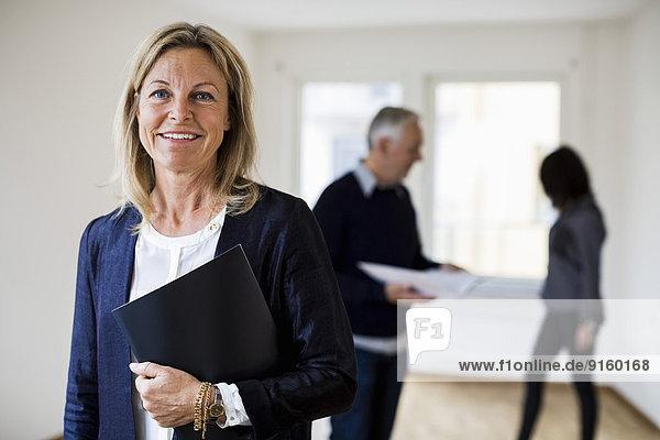 Porträt eines selbstbewussten Immobilienmaklers mit Kollegin und Frau im Hintergrund zu Hause