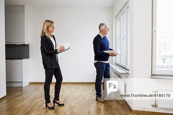 Reife Immobilienmakler schauen durchs Fenster zu Hause