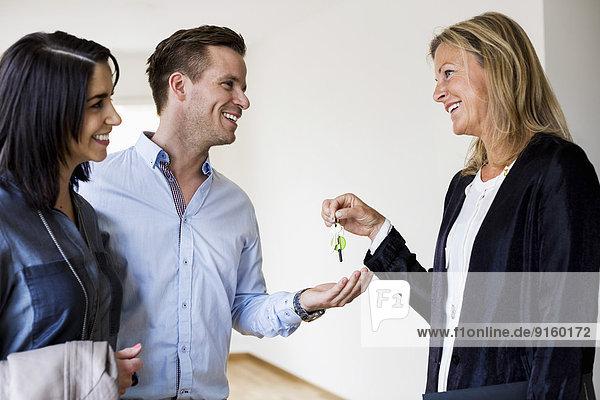 Glückliche Immobilienmakler geben Schlüssel zu Paar im neuen Haus