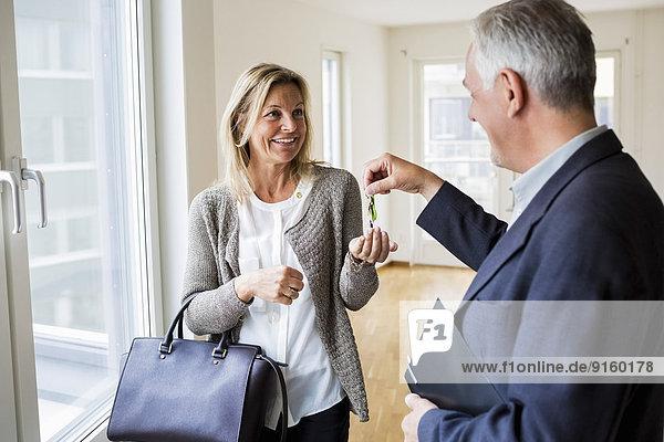 Glückliche männliche Immobilienmaklerin übergibt Schlüssel an Frau im neuen Haus