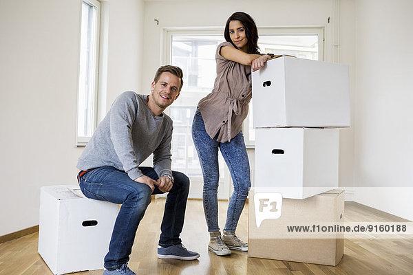 Volle Länge des glücklichen Paares mit Umzugskartons zu Hause