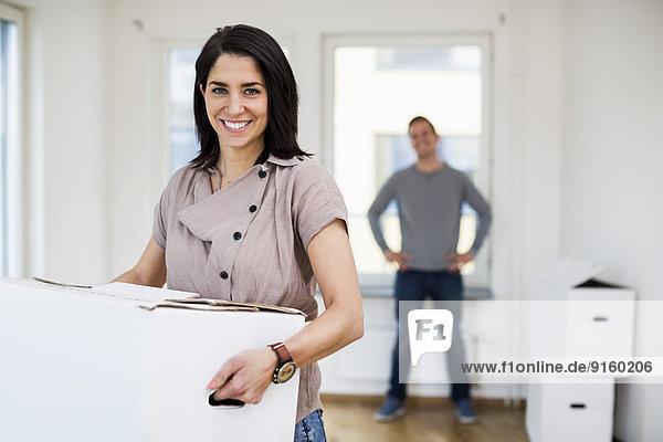 Porträt einer fröhlichen Frau  die eine Umzugskiste mit einem Mann im Hintergrund zu Hause trägt.