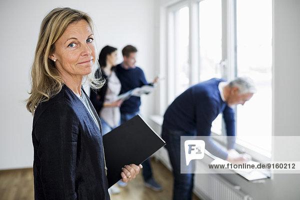 Porträt eines selbstbewussten reifen Immobilienmaklers mit Kollege und Ehepaar zu Hause