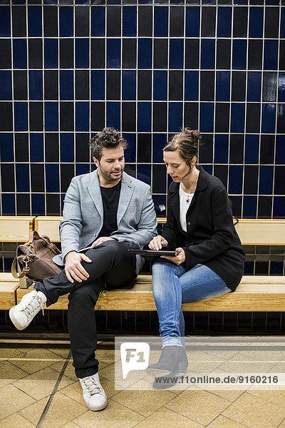 Volle Länge der Geschäftsleute  die über digitale Tabletten diskutieren  während sie auf einer Bank in der U-Bahn-Station sitzen.