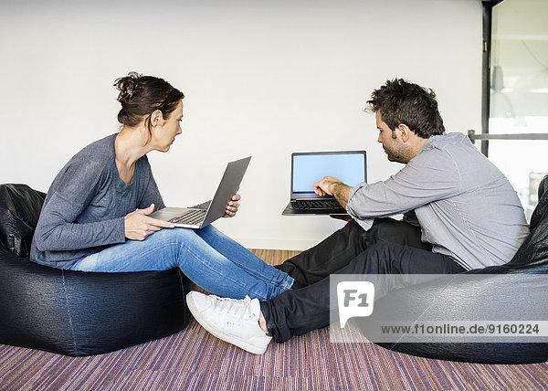Volle Länge der Geschäftsleute  die über Laptops diskutieren  während sie im Büro auf Sitzsäcken sitzen.