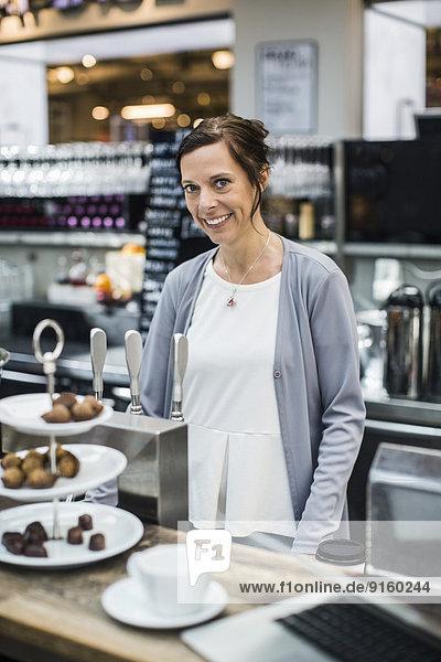 Porträt der lächelnden reifen Besitzerin am Cafe Tresen