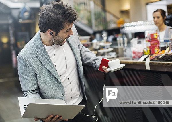 Panik mittleren Erwachsenen Mann hält Laptop und Kaffee im Café