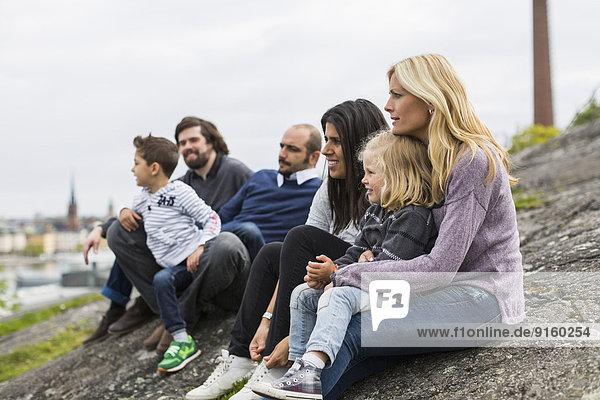 Homosexuelle Familien entspannen sich auf dem Felsen am Seeufer