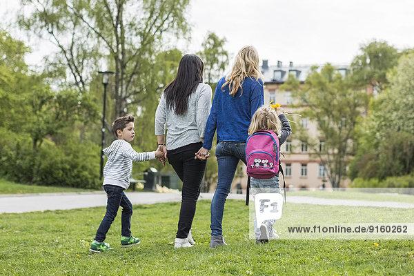 Rückansicht der weiblichen homosexuellen Familie beim Spaziergang im Park